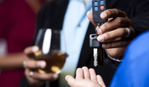 Homem com drink em mãos entregando chaves do carro para outra pessoa