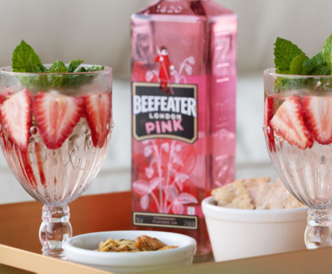 garrafa de beefeater pink entre copos com a bebida, morangos e hortelã