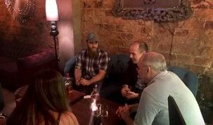 pessoas sentadas em volta de uma mesa conversando
