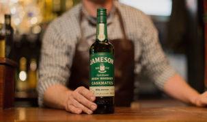 Bartender segurando garrafa de jameson caskmates ipa