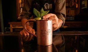 barman colocando hortelã em caneca de cobre