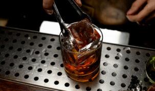 barman colocando gelo cristal em um copo baixo