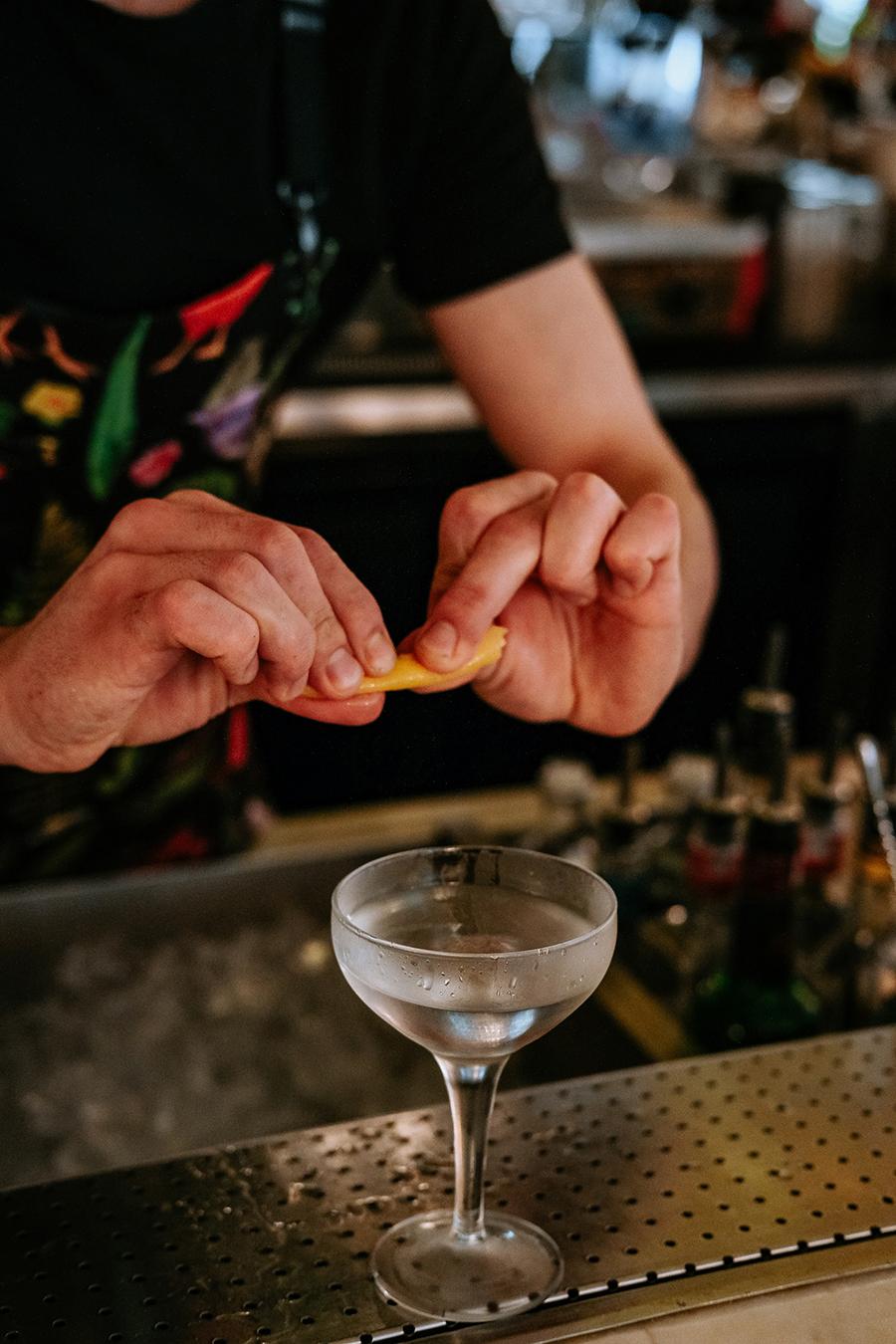 bartender torcendo zest de laranja
