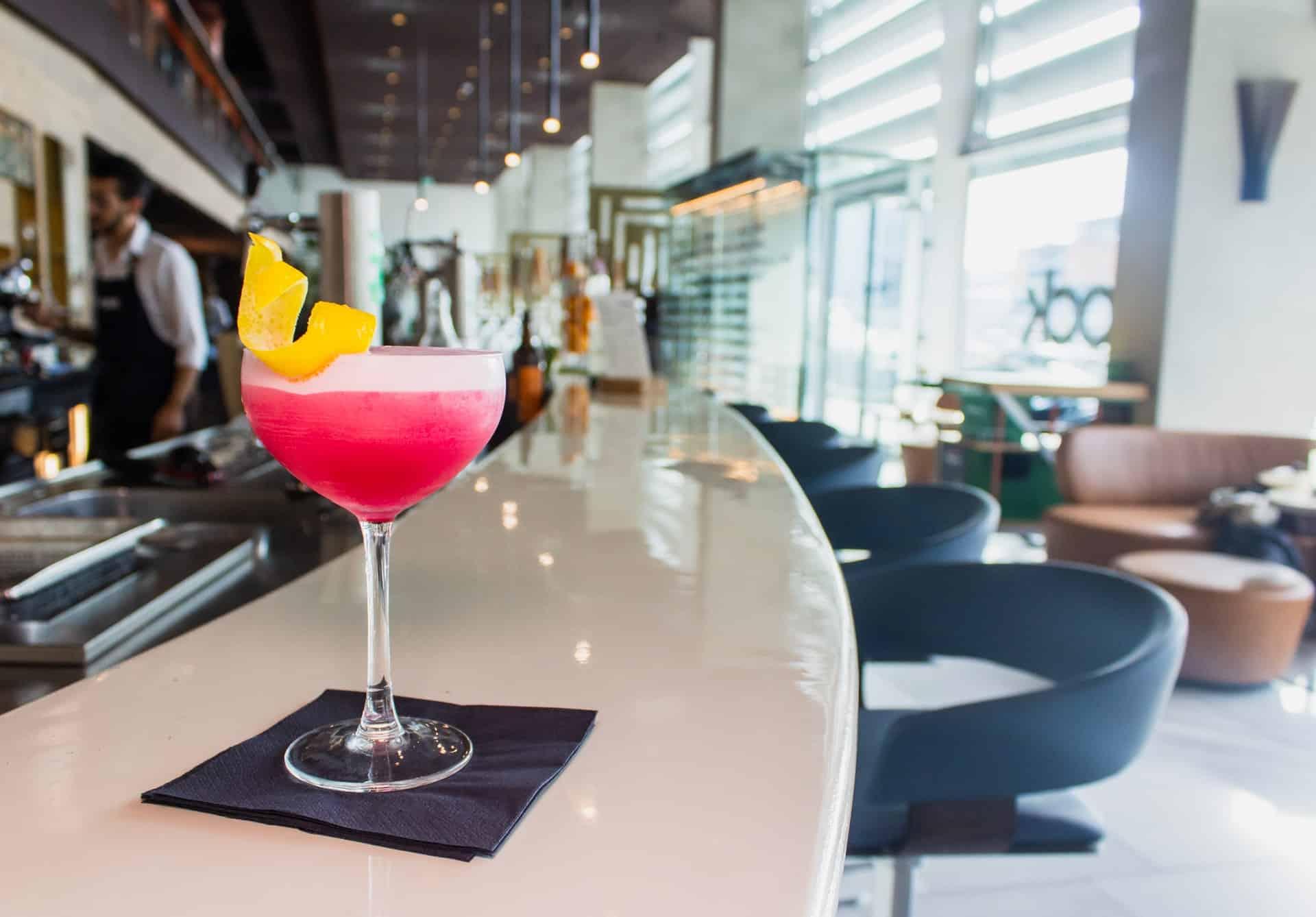 cocktail rosa sobre o balcão de um bar