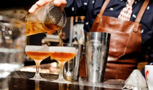 bartender colocando drink em duas taças